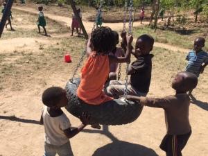 School Kids Enjoying a Tire Swing Set