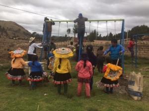 Quechua Children Watching Swing Set Installation