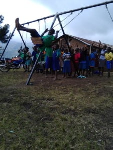 Children Enjoying the Swing Set at Sacred Heart Nursery and Primary School in Kiduku, Uganda